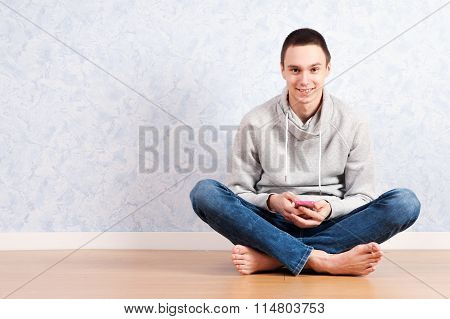 Portrait Of Young Man Sitting On The Floor Using A Cellphone, Isolated. Ready For Your Design
