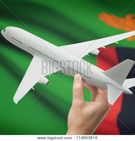 Airplane In Hand With Flag On Background - Zambia