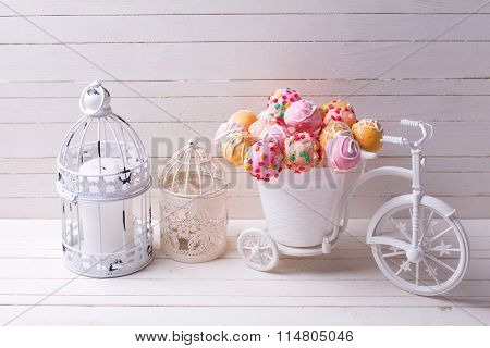 Cake Pops  In Decorative Bicycle And Candles  On White Wooden Background.