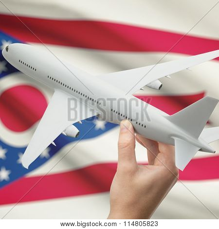 Airplane In Hand With Us State Flag On Background - Ohio
