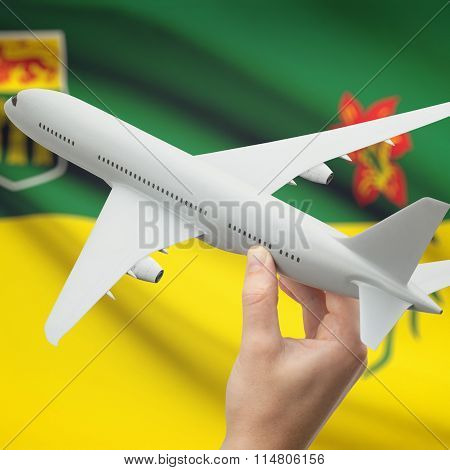 Airplane In Hand With Canadian Province Flag On Background - Saskatchewan