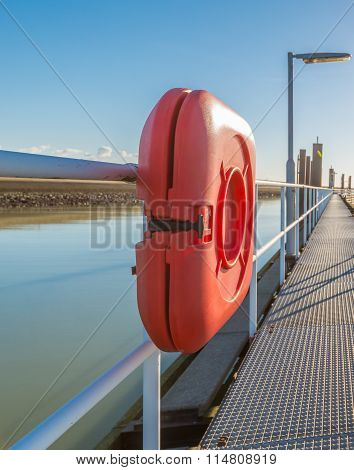 Orange Life Buoy Equipment On A Long Steel Jetty