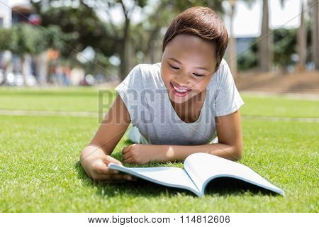 beautiful young african american woman lying on the grass and reading a book