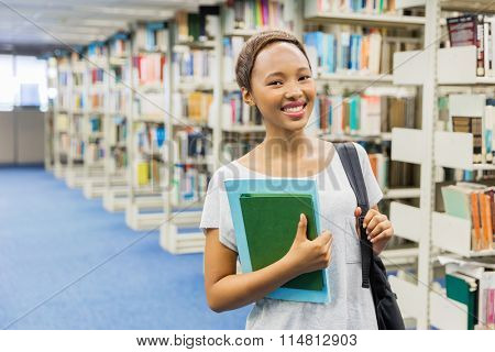 pretty young african american college student standing in library