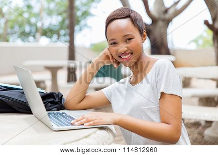 portrait of young black college girl using laptop