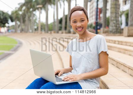 carefree pretty african college girl with laptop on campus
