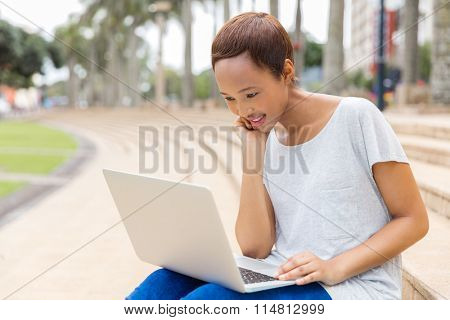 pretty young african woman using laptop computer outdoors