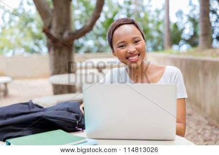 pretty african college student relaxing outdoors and looking at the camera