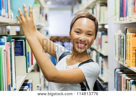beautiful young african student in library searching for books