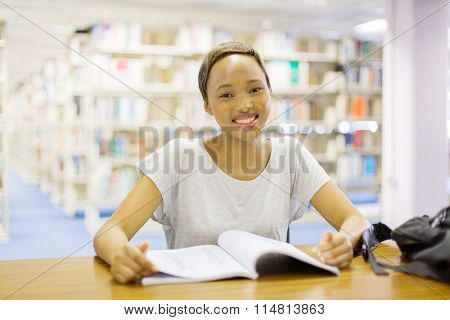 portrait of happy young female african college student in library