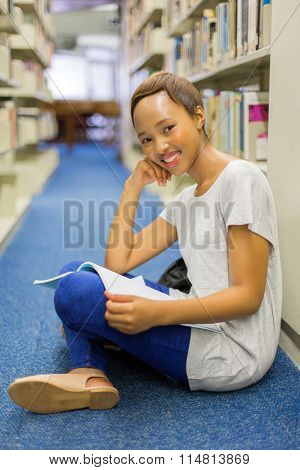 gorgeous female african student sitting on library floor and reading