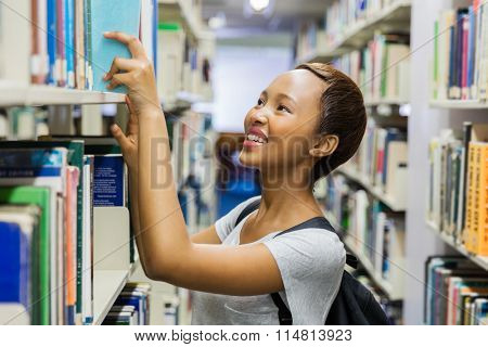 happy young african college student reaching for a book in library