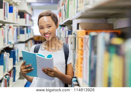 gorgeous afro american college girl reading a book in library
