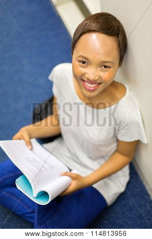 overhead view of happy african college girl reading a book