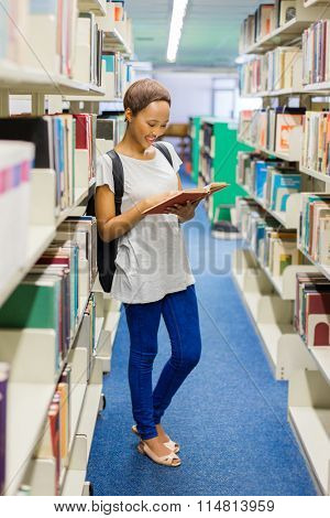 pretty young female african university student reading a book in library