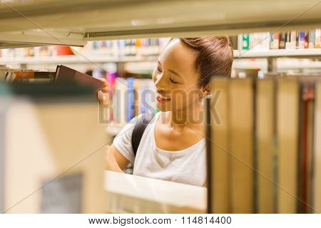 attractive young female college student in library looking for books in library
