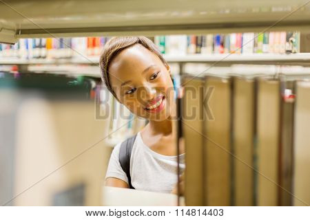 happy african american college student behind bookshelf in library