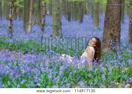 Pretty young woman with long hair in bluebells springtime forest
