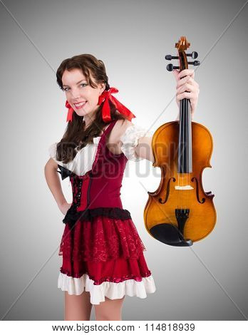 Young woman playing violin against gradient