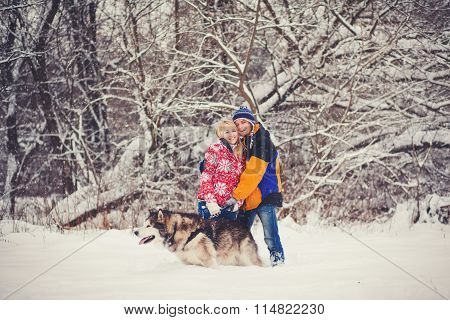Happy Couple Standing With A Dog