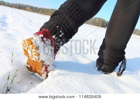 Walk on snowy path. Close up of legs in winter shoes.