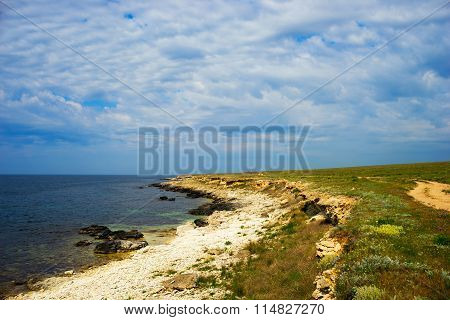 Deserted Coast Of The Black Sea With Picturesque Clouds.