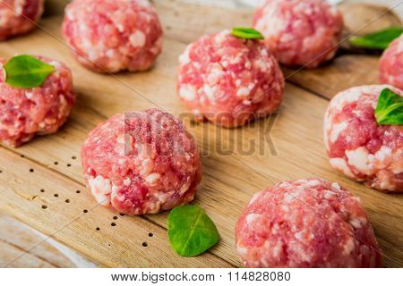 Raw Meatballs Of Beef And Pork On A Wooden Board