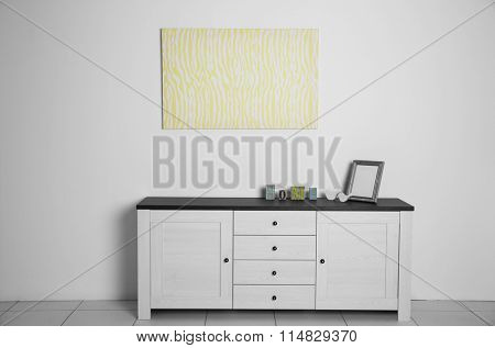Abstract picture with commode, frame and inscription home on a white wall background