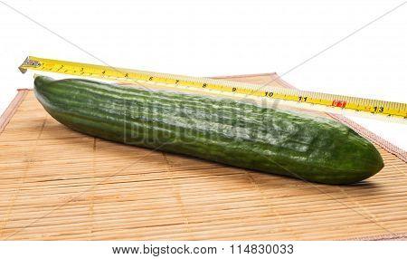 Big Yellow Centimeter Measuring A Green Cucumber.