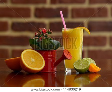 fresh juice composition with red flowers in a watering can and halves fruits deco oranges and lime b