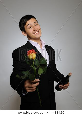 Handsome Romantic Young Man Holding Rose Flower And Vine Bottle  Prepared For A Valentines Day. Gray