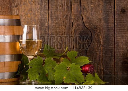 Glass Of Wine With Bottle In Grapeleaves