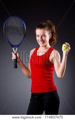 Woman tennis player against dark background