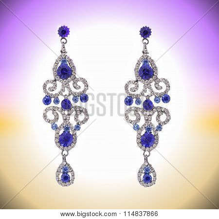 long earring with blue stones and zircons on a white background