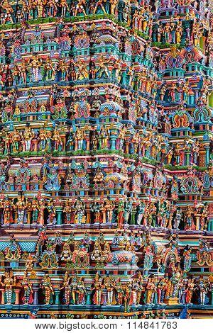Hindu temple gopura (tower) with statues of deities close up. Menakshi Temple, Madurai, Tamil Nadu, India