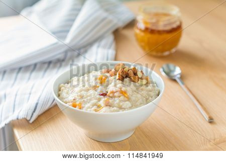 Healthy breakfast: oats porridge with almonds, dried fruits and honey on wooden table