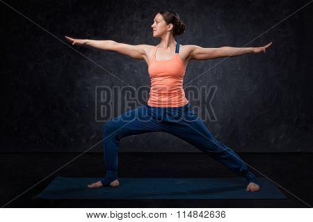 Beautiful sporty fit yogini woman practices yoga asana Virabhadrasana 2 - warrior pose 2 on dark background