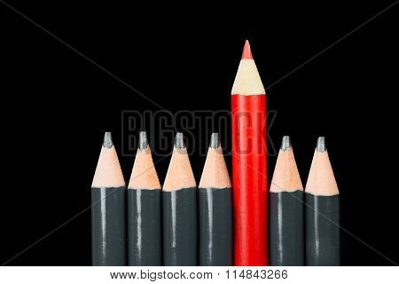 One red pencil with black ones