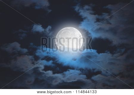 Moon among the clouds on a midnight sky.