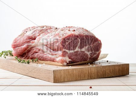 Photo of raw meat. Pork neck with herbs and green thyme on wooden board