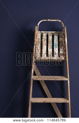 Old Wooden Stepladder Leaning Over A Blue Backdrop