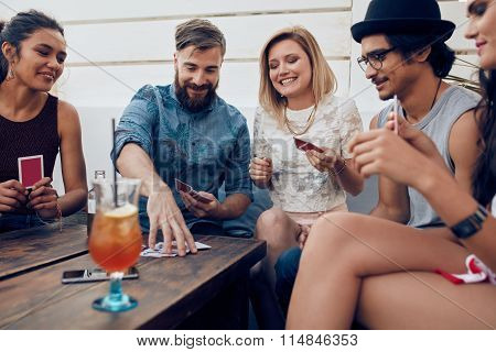 Group Of Friends In A Party Playing Cards