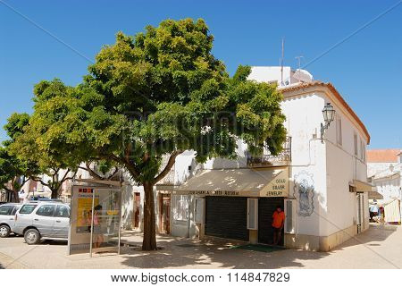 People hide in the shadow on a hot day at the street in Lagos, Portugal.
