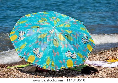 Sunshades And Clothes On A Sea Beach