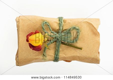 Paper Wrapped Gift With Jute Bow And Rose On White