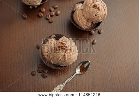 Coffee ice cream in chocolate bowl on wooden background