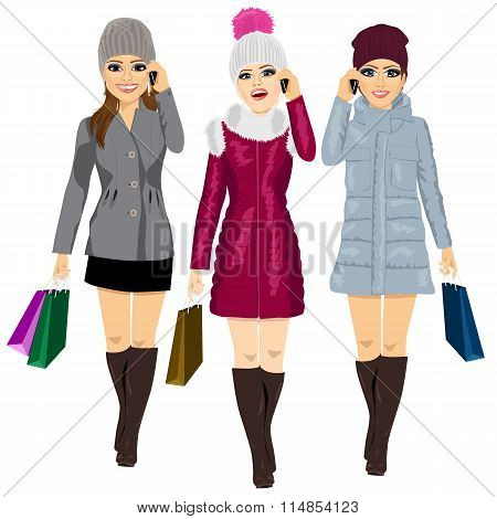 three young fashion women with shopping bags in winter clothes talking on the phone and walking forw