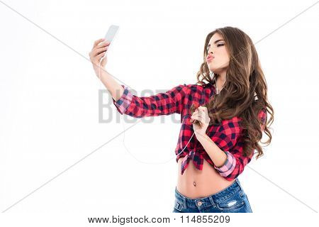 Cute lovely young woman making duck face and taking selfie with mobile phone over white background