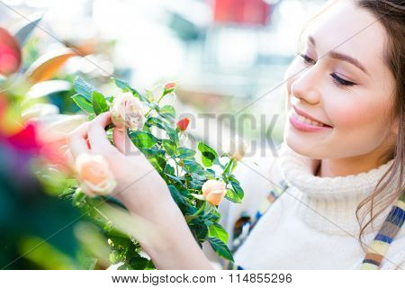 Closeup of charming cheerful woman gardener looking and enjoying roses in garden center