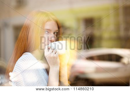 Beautiful redhead woman drinking coffee and looking at window